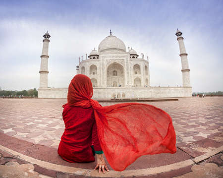 Woman in red costume with flattering scarf sitting near Taj Mahal in Agra, Uttar Pradesh, India Stock Photo - 40618780