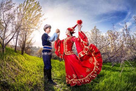 Mujer kazajo bailando en el vestido rojo con el hombre en el jardín de la manzana de primavera en Almaty, Kazajstán, Asia Central