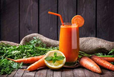 Fresh carrot juice with lemon and mint on wooden background
