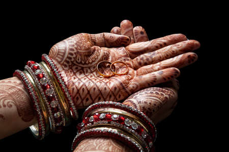 marriages: Woman hands with henna holding two golden wedding rings on black background