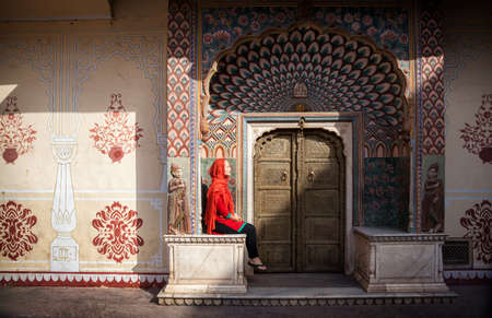Woman in red scarf sitting near Lotus gate in City Palace of Jaipur, Rajasthan, India