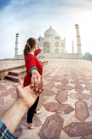 Woman in red Indian costume holding man by hand and pointing to Taj Mahal in Agra, Uttar Pradesh, India Banco de Imagens