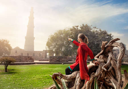 new delhi: Woman in red costume pointing at Qutub Minar tower in Old Delhi, India Stock Photo
