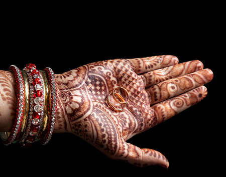mehendi: Wedding rings in Woman palm with henna painting on black background Stock Photo