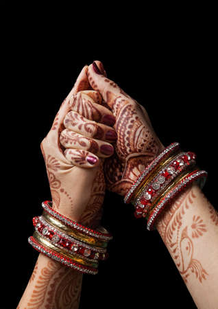 Woman hands with henna in shell mudra on black background