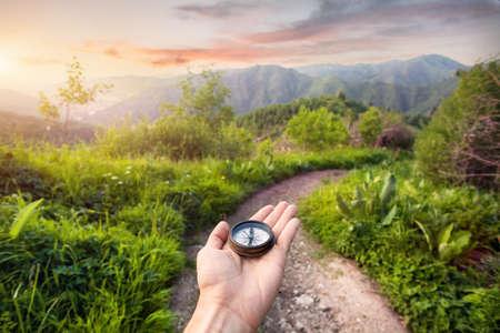 kompas: Ruce s kompasem na horské silnici při západu slunce oblohu v Kazachstánu, Střední Asii