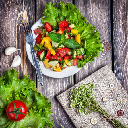 Fresh green salad and recipe book on the wooden table in the kitchen Stock Photo - 41795703
