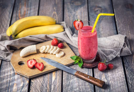 Banana and strawberry smoothie on wooden background 免版税图像