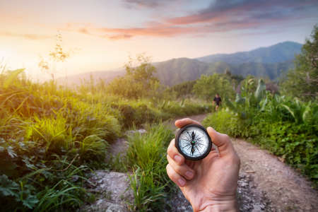 Hand met kompas op bergweg bij zonsondergang hemel in Kazachstan, Centraal-Azië Stockfoto - 41851649