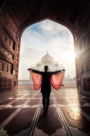 donna farfalla: Donna con la sciarpa rossa in posa vicino a Taj Mahal ad Agra, Uttar Pradesh, India