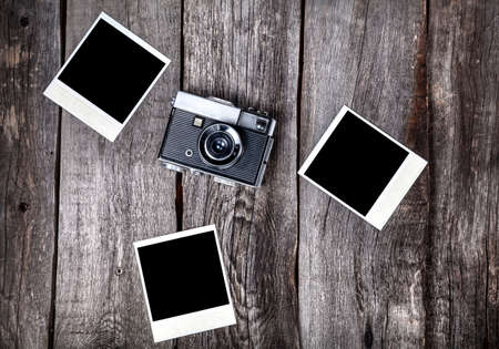 Old film camera and polaroid photos with space for pictures on the wooden background Stockfoto