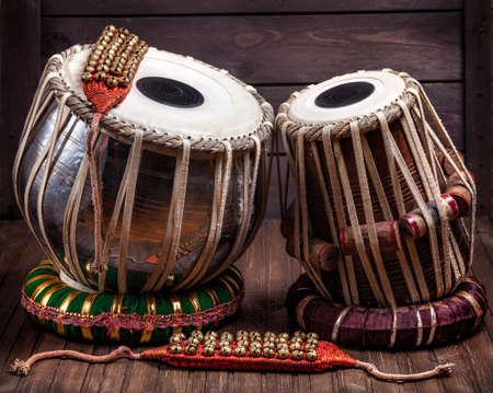 drum: Tabla drums and bells for Indian dancing on wooden background Stock Photo