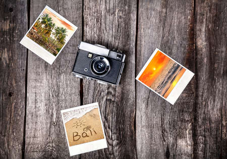 vintage travel: Old film camera and polaroid photos with Bali tropical beaches on the wooden background