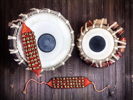 bharatanatyam: Tabla drums and bells for Indian dancing on wooden background Stock Photo