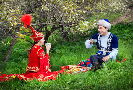 kazakh: Kazakh couple drinking tea on the green grass in apple garden of Almaty, Kazakhstan, Central Asia Stock Photo