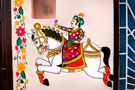 indian culture: Traditional Rajasthan painting on the house wall of king riding on the horse in Udaipur, Rajasthan, India Stock Photo