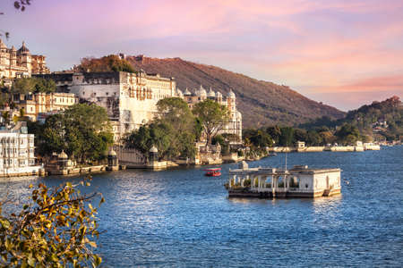 Lake Pichola with City Palace view at pink sunset sky in Udaipur, Rajasthan, India