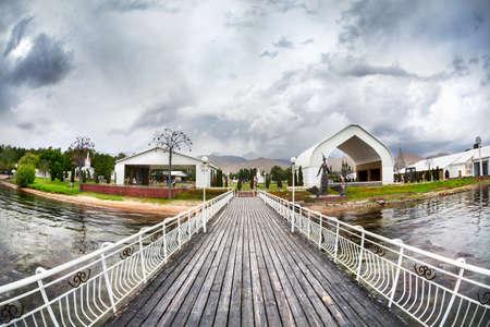 issyk kul: Pier in Ruh Ordo cultural complex near Issyk Kul lake at overcast sky in Cholpon Ata, Kyrgyzstan