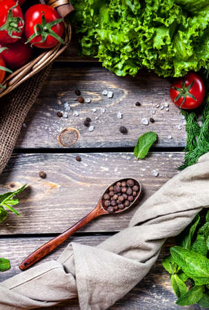 pepe nero: Cucchiaio con pepe nero spezie, pomodori e insalata verde sul tavolo di legno in cucina