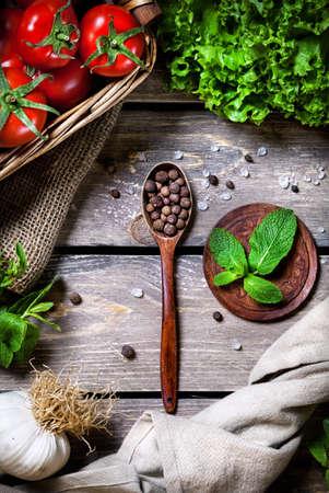 portadas de libros: Cuchara con especias negro pimienta, menta, tomate y ensalada verde en la mesa de madera en la cocina