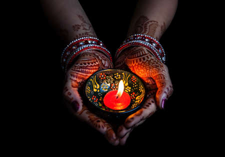 Woman hands with henna holding lit candle isolated on black background with clipping path Stockfoto
