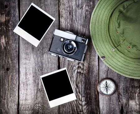 Old film camera, photos with space for pictures, hat and compass on the wooden background