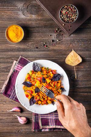Mann isst Herbstsalat mit Kürbis, Karotten, Tomaten und Basilikum auf dem Tisch aus Holz mit Gewürzen