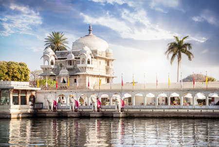on lake: Luxury hotel on the Pichola lake at blue cloudy sky in Udaipur, Rajasthan, India Stock Photo