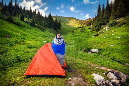 Tourist in sleeping bag near orange tent in the mountains in Kazakhstan, central Asia