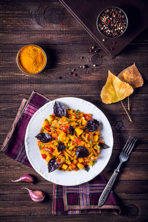 Autumn salad with pumpkin, carrot, tomato and basil on the wooden table with spices in the kitchen