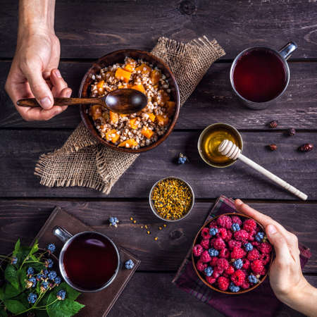 comiendo cereal: Desayuno romántico sano con gachas de calabaza y bayas en la aldea de la casa de verano