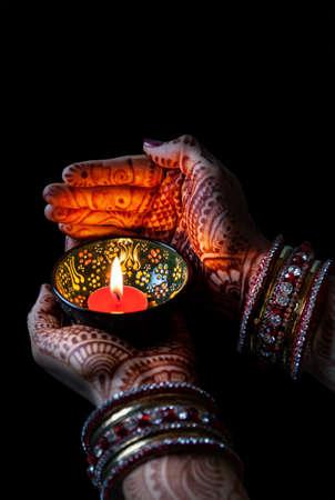 Vrouw handen met henna bedrijf brandende kaars geïsoleerd op zwarte achtergrond met het knippen van weg Stockfoto - 42855593