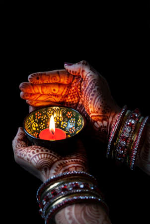 lady with the lamp: Woman hands with henna holding lit candle isolated on black background with clipping path Stock Photo