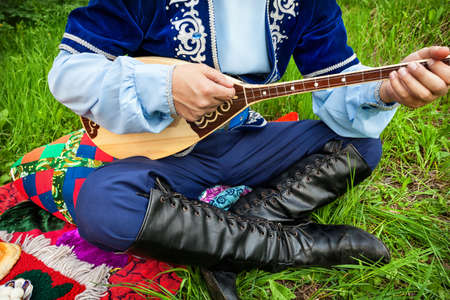 kazakh: Man in traditional Kazakh costume playing dombra instrument on the green grass in apple garden of Almaty, Kazakhstan, Central Asia