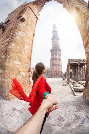 Vrouw in het rood kostuum toonaangevende man met de hand om Qutb Minar toren in Delhi, India