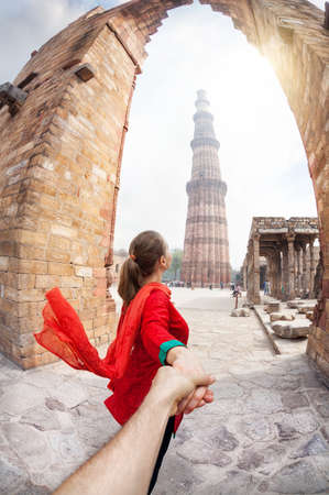 Woman in red costume leading man by hand to Qutub Minar tower in Delhi, India