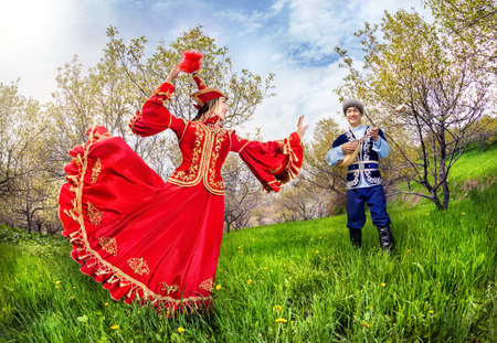 kazakh: Kazakh woman dancing in red dress and man playing dombra at Spring Blooming garden in Almaty, Kazakhstan, Central Asia