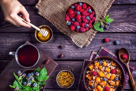 desayuno romantico: Desayuno saludable con gachas de calabaza, bayas y té de hierbas con miel en el pueblo de la casa de verano Foto de archivo