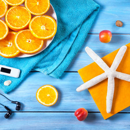 Oranges, towel, headphones and starfish on blue wooden background. Summer holiday concept