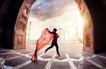 baile: Mujer con pañuelo rojo bailando cerca de Taj Mahal en Agra, Uttar Pradesh, India