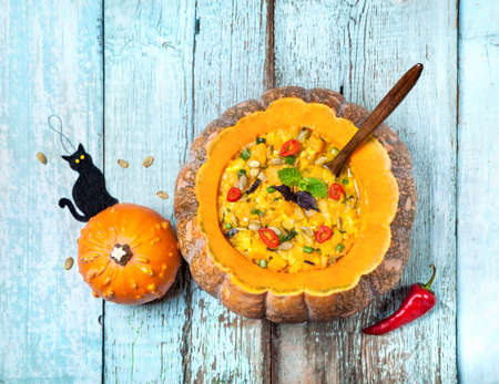 pumpkin seed: Soup with lentil in the carved pumpkin and black cat toy on the blue wooden background at Halloween party Stock Photo