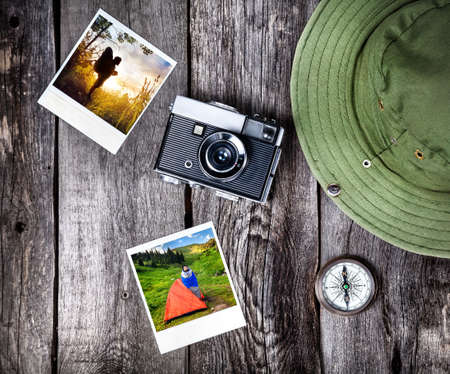 Old film camera, photos with tourist in nature, hat and compass on the wooden background