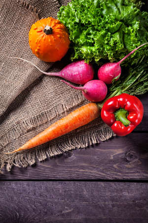 veggies: Fresh vegetables on sackcloth and wooden table in the kitchen