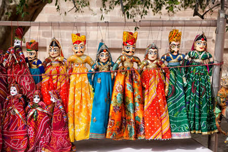 Colorful Rajasthan puppets hanging in the shop of Jodhpur City Palace, India