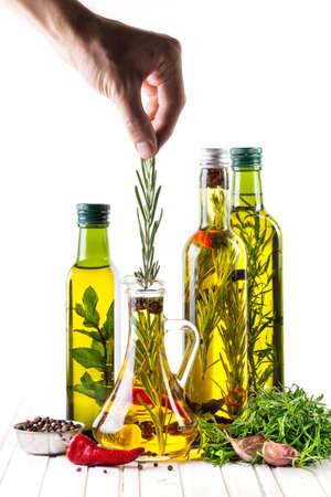 mamadera: Hombre que pone el romero en la botella con aceite, hierbas y especias en el fondo blanco