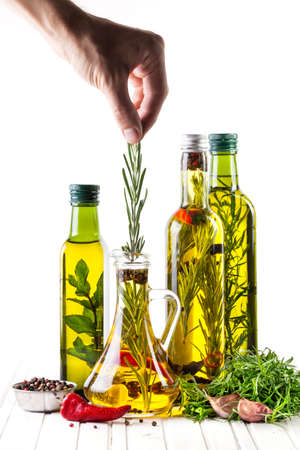 Man putting rosemary in the bottle with oil, herbs and spices on white background Фото со стока