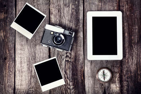 Old film camera, tablet and photos with space for pictures on the wooden background Stock Photo
