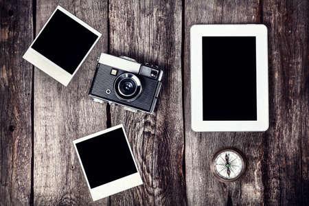 Oude filmcamera, tablet en foto's met ruimte voor foto's op de houten achtergrond
