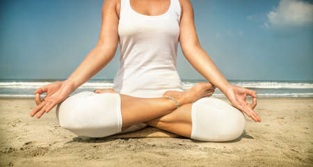 Woman doing yoga meditation in white costume on the beach in Goa, India Stock Photo - 43393581