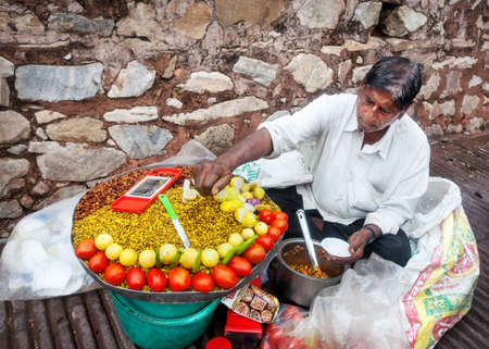 spice market: JAIPUR, RAJASTHAN, INDIA - MARCH 01, 2015: Man selling spicy snacks with beans and vegetables near Amber Fort Editorial